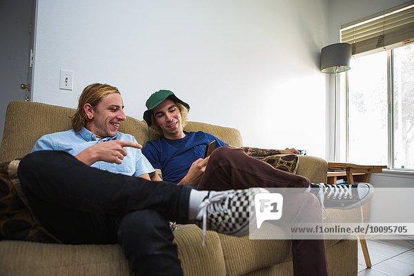 Zwei junge Männer sitzen auf dem Sofa und schauen auf das Smartphone.