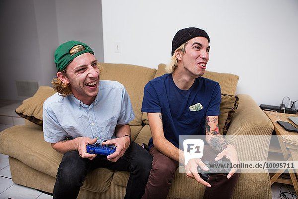 Two young men sitting on sofa  playing video game
