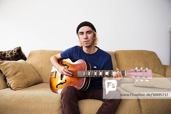 Junger Mann sitzt auf dem Sofa und spielt Gitarre.