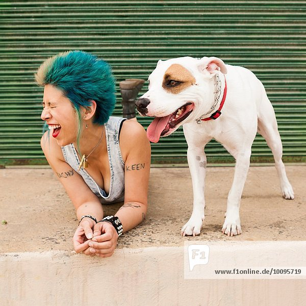 Junge Frau mit bunten Haaren  auf dem Boden neben dem Hund liegend  lachend