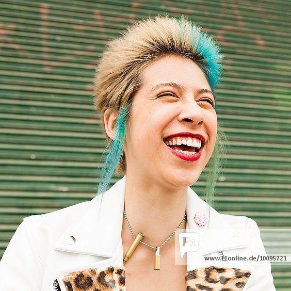 Porträt einer jungen Frau mit buntem Haar  lachend  im Freien
