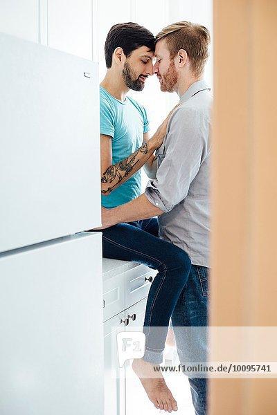 Männliches Paar in der Küche  von Angesicht zu Angesicht  umarmend