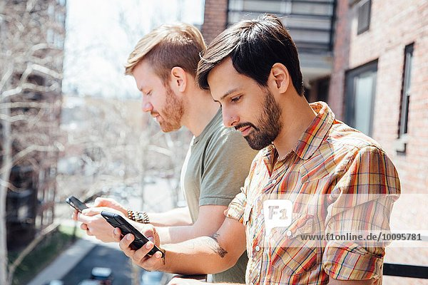 Male couple standing on balcony  looking at smartphones