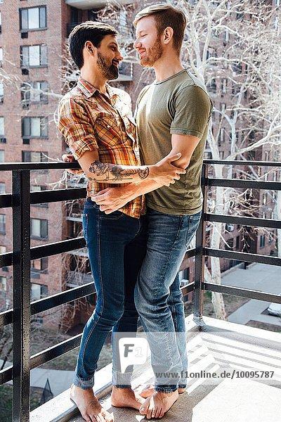 Männliches Paar auf dem Balkon stehend  umarmend  von Angesicht zu Angesicht