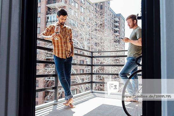 Männliches Paar steht auf dem Balkon  steht voneinander entfernt  trinkt Wein und schaut auf das Smartphone.