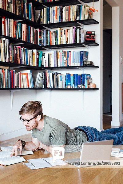 Mittlerer Erwachsener Mann  der auf dem Boden liegt und durch Bücher schaut.