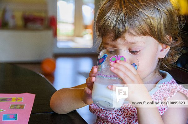 Süßes  junges Mädchen trinkt ein Glas Milch am Küchentisch.
