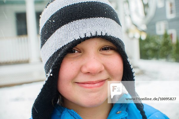 Close up portrait of girl wearing black and white striped hat in snowy garden