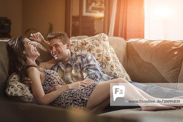 Romantisches junges Paar lacht auf dem Sofa im Wohnzimmer