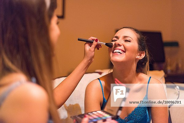 Zwei junge Frauen  die sich schminken.