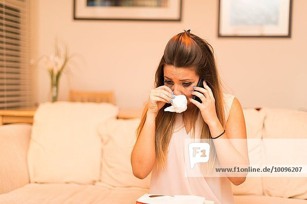 Young woman having telephone conversation  crying