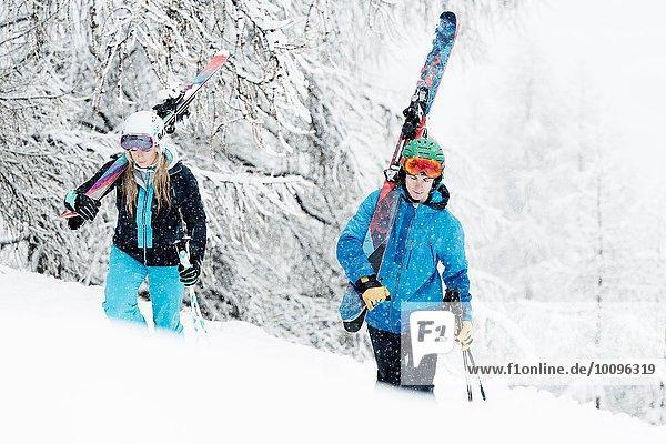 Mann und Frau mit Skiern im Schnee unterwegs