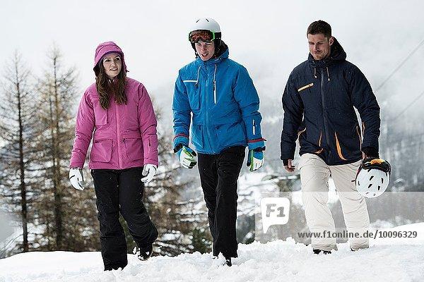 Drei Freunde in Skibekleidung beim Wandern im Schnee