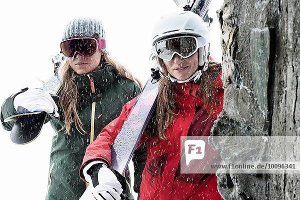 Frauen mit Skibrille  die Skier halten.