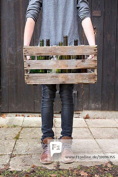 Teenager Junge mit leeren Flaschen in Holzkiste