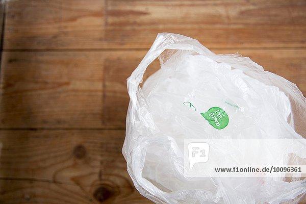 Recycelbare Einkaufstaschen aus Kunststoff auf Holzboden