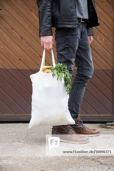 Teenager-Junge mit wiederverwendbaren Einkaufstaschen voller frischem Obst und Gemüse