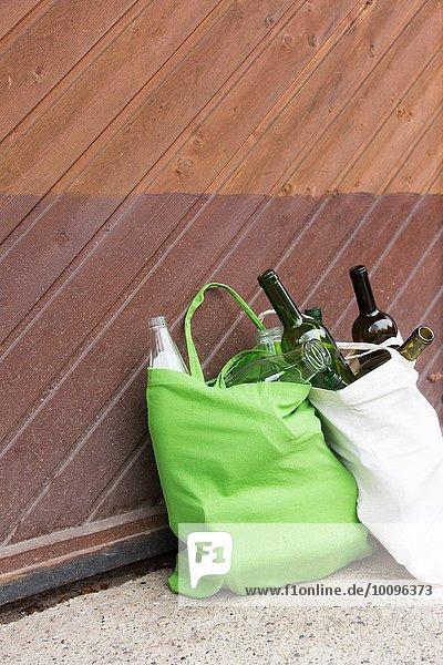 Zwei wiederverwendbare Einkaufstaschen voller Flaschen für das Recycling im Hof