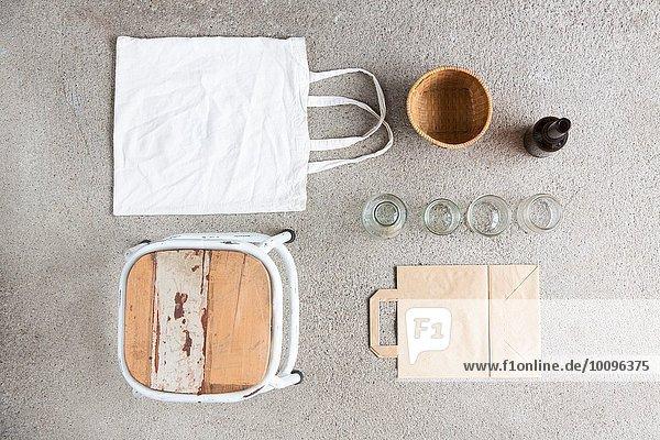 Überkopf-Stilleben von Hocker  wiederverwendbarer Einkaufstasche und recycelbarem Papier und Flaschen