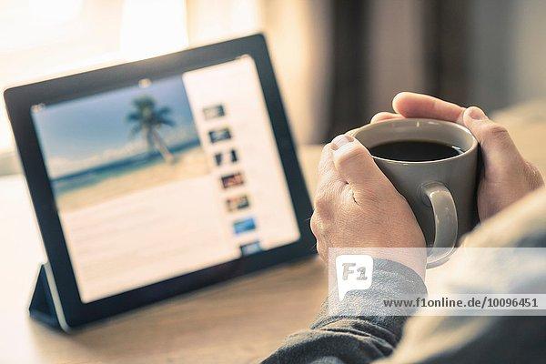 Hände des Mannes beim Kaffeetrinken mit digitalem Tablett auf dem Schreibtisch