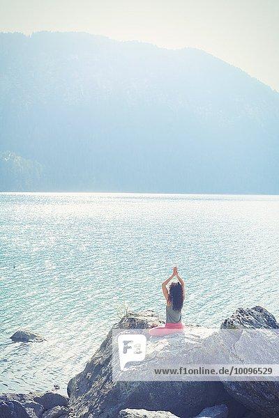 Mittlere erwachsene Frau  auf Felsen sitzend  am See  in Yogastellung  Rückansicht