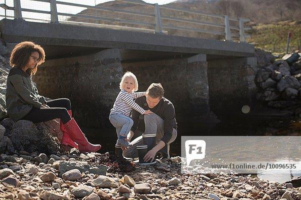 Vater setzt Gummistiefel auf Sohn bei Fußgängerbrücke auf