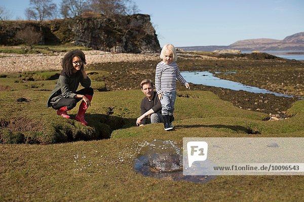 Boy throwing rock into puddle  Isle of Skye  Hebrides  Scotland