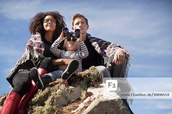 Familie auf Felsen sitzend  Junge mit Binokularen
