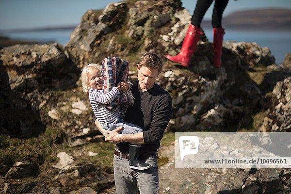 Vater trägt den Sohn in den Armen
