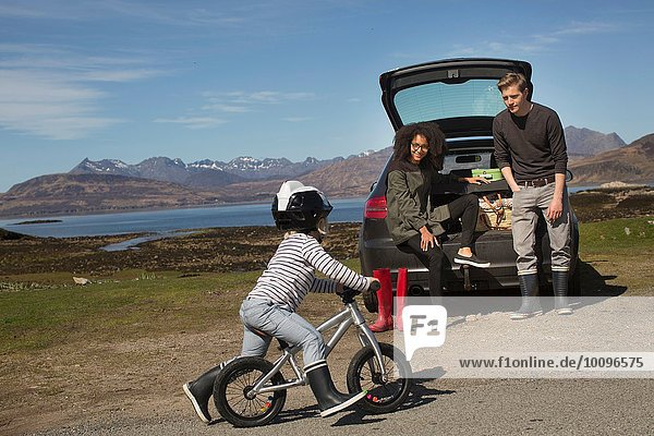 Eltern beobachten Sohn Fahrrad fahren  Loch Eishort  Isle of Skye  Hebrides  Schottland