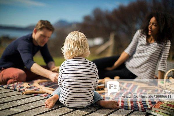 Junge sitzend auf Holzterrasse  Rückansicht