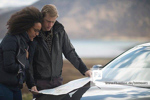 Mittleres erwachsenes Paar mit dem Auto mit Karte