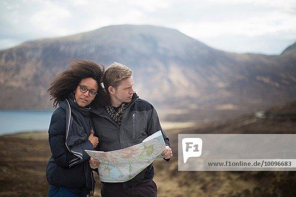 Mittleres erwachsenes Paar in den Bergen mit Karte