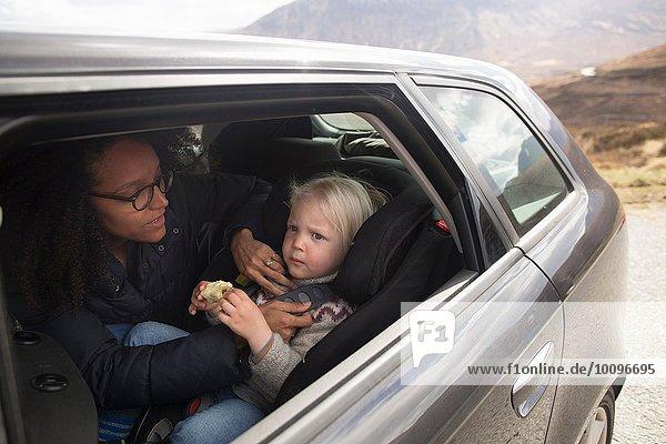 Mutter stellt den Sicherheitsgurt des Sohnes im Auto ein