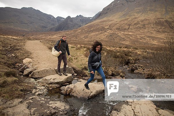 Frau überquert Bach  Fairy Pools  bei Glenbrittle  Isle of Skye  Hebriden  Schottland