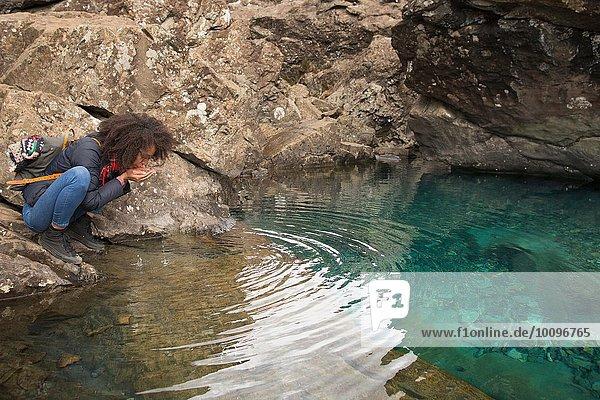 Frau trinkt Wasser aus hohlen Händen  Fairy Pools  Isle of Skye  Hebrides  Schottland