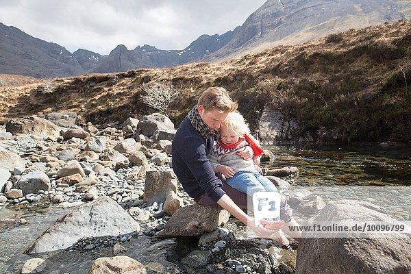 Vater und Sohn sitzen auf Felsen  Fairy Pools  Isle of Skye  Hebrides  Schottland