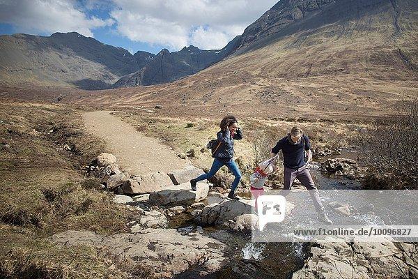 Family crossing stream  Fairy Pools  Isle of Skye  Hebriden  Schottland