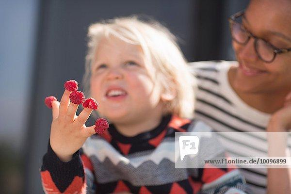 Junge mit Himbeeren an den Fingern  Mutter schaut zu.
