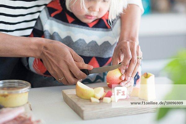 Mutter hilft Sohn Apfel hacken