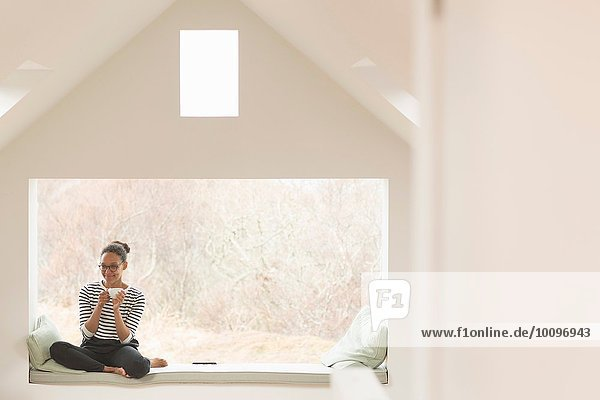 Mittlere erwachsene Frau sitzend im Fenstersitz
