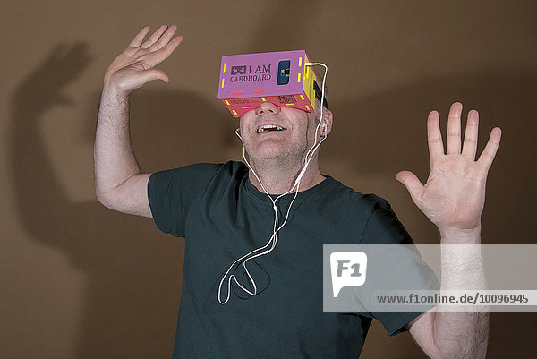 Mann trägt I AM CARDBOARD 45mm Focal Length Virtual Reality Google Cardboard-VR-Brille mit Samsung Galaxy S5 Android Smartphone und In-Ear Kopfhörer  Hände oben