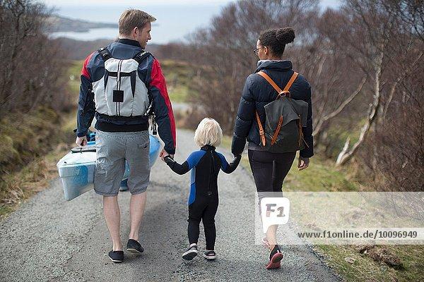 Familienwanderung auf der Landstraße mit den Händen  Rückansicht