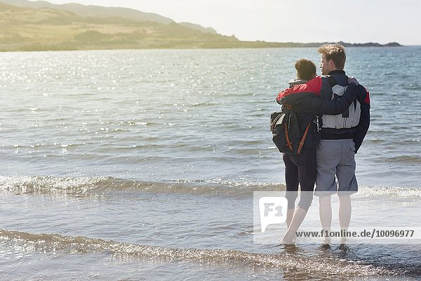 Mittleres erwachsenes Paar mit Armen umeinander am Strand  Loch Eishort  Isle of Skye  Hebrides  Schottland