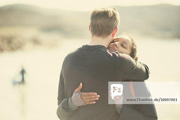 Mittleres erwachsenes Paar  das sich im Sonnenlicht umarmt.