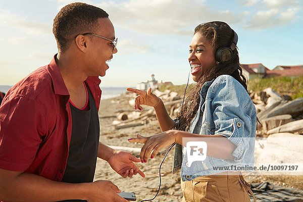 Junges Paar am Strand mit Kopfhörern  von Angesicht zu Angesicht lachend