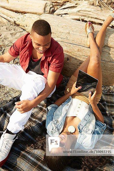 Junges Paar entspannt gemeinsam am Strand mit digitalem Tablett  Draufsicht