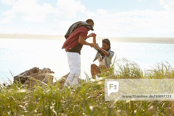 Junger Mann hilft junger Frau beim Klettern