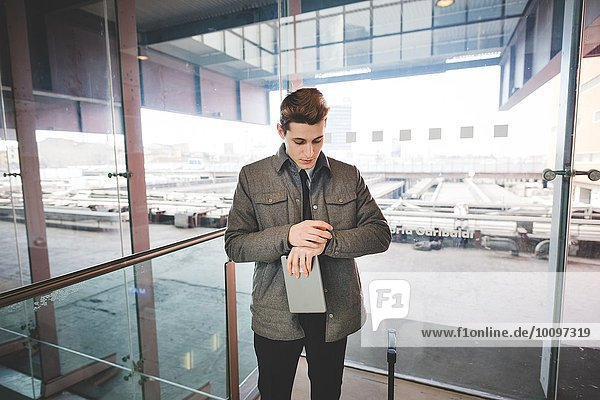 Portrait of young businessman commuter checking wristwatch for time.