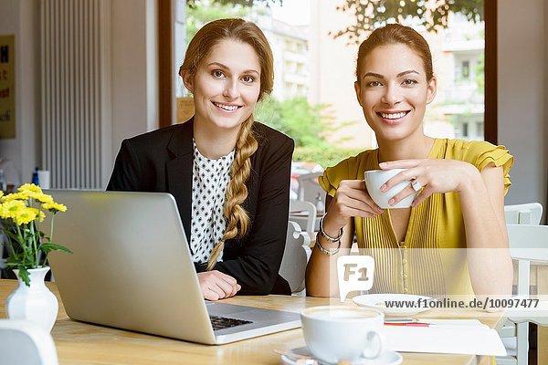 Porträt zweier junger Frauen beim Kaffeetrinken im Café